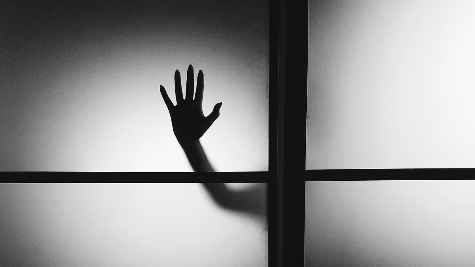 B&W hand against a glass wall