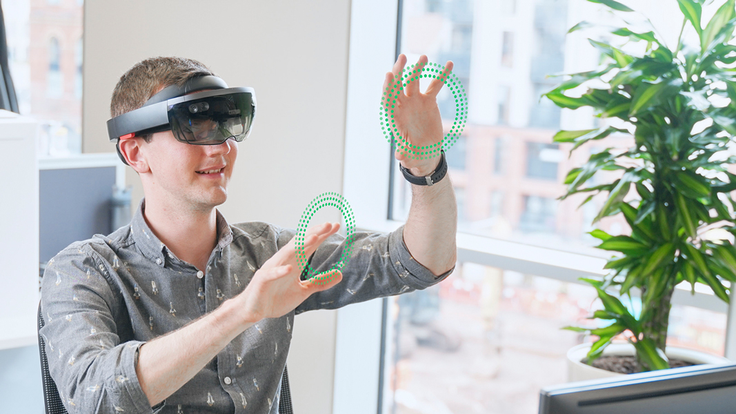 Man with AR head set, with green particles in the workplace