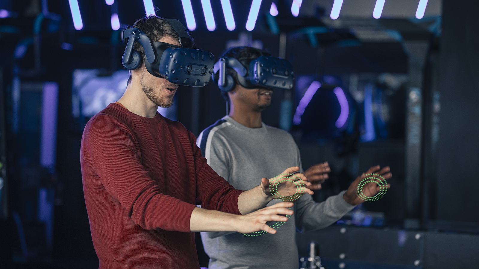 Two men with VR headsets on with green particles