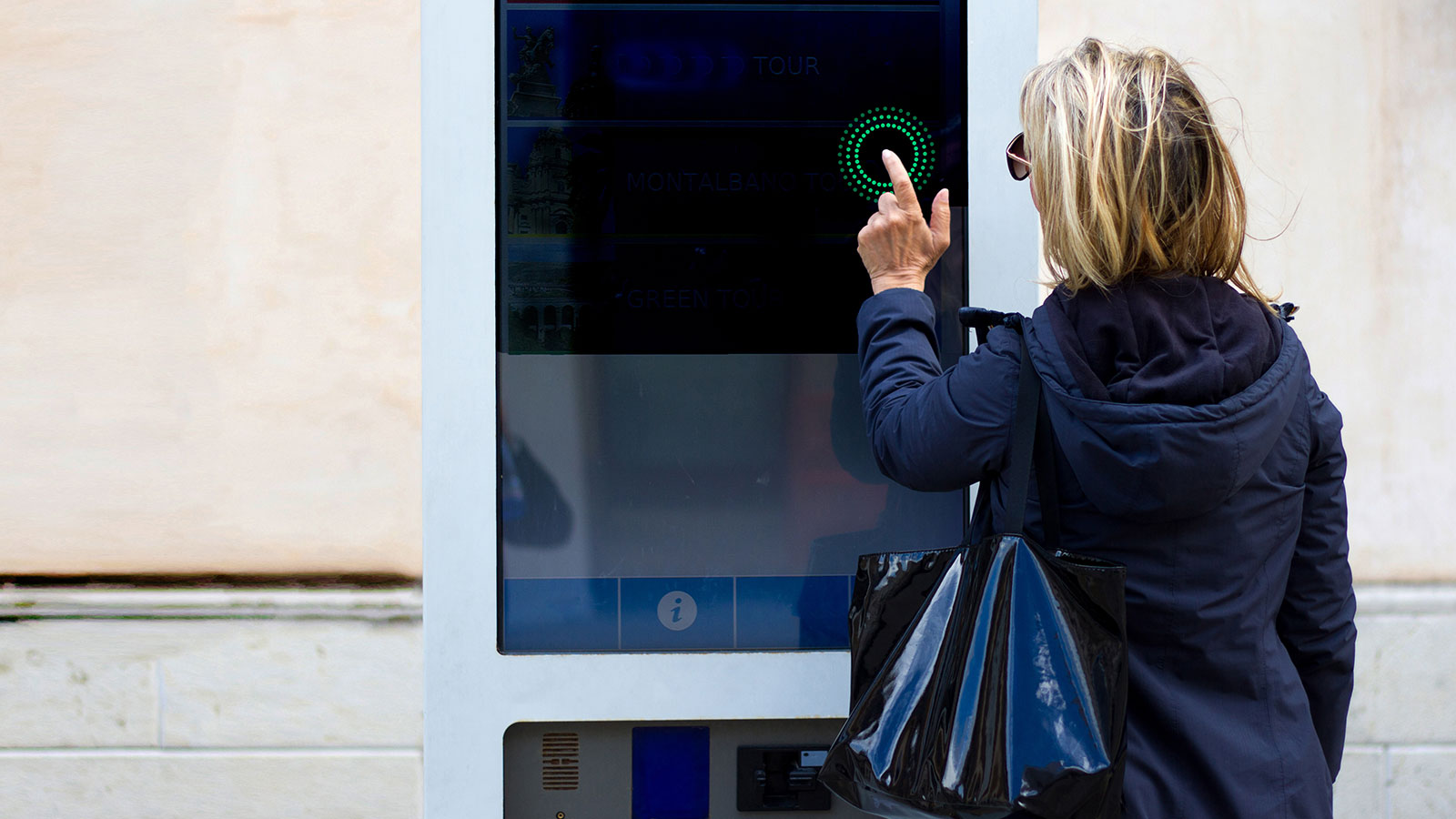 Woman using touchless technology instead of a public touchscreen