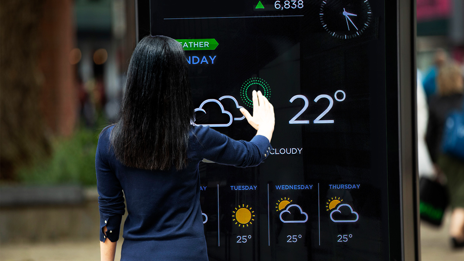 Woman interacting with a hygiene touchless interactive kiosk