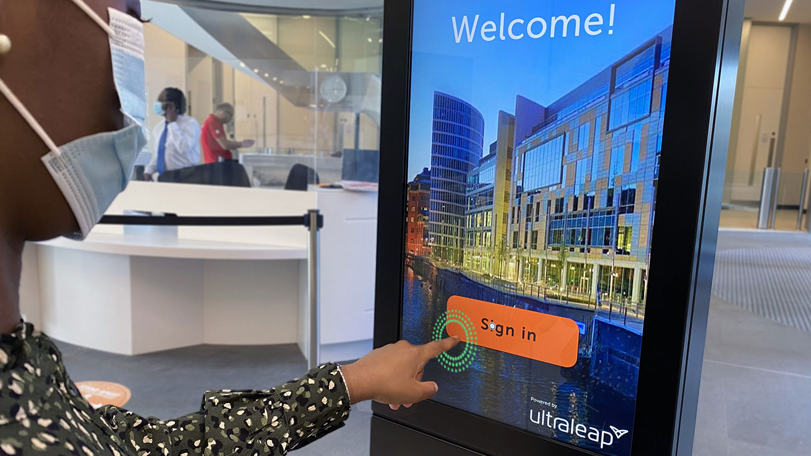 Woman using TouchFree software on an interactive kiosk screen